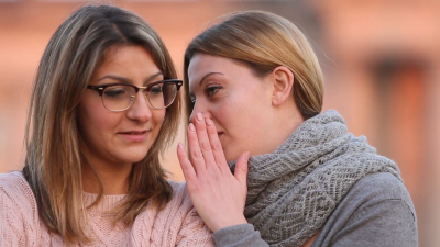 young-false-blond-woman-whispering-secret-in-another-womans-ear-outdoors_r-ykjkhx__F0000.png